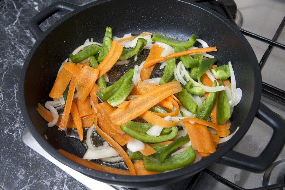 Saltare la cipolla, le carote e i peperoni in abbondante olio di semi.