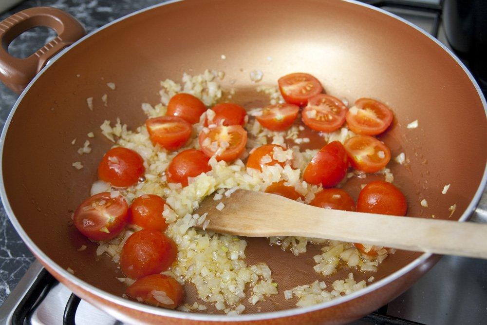 Soffriggiamo la cipolla e i pomodorini.