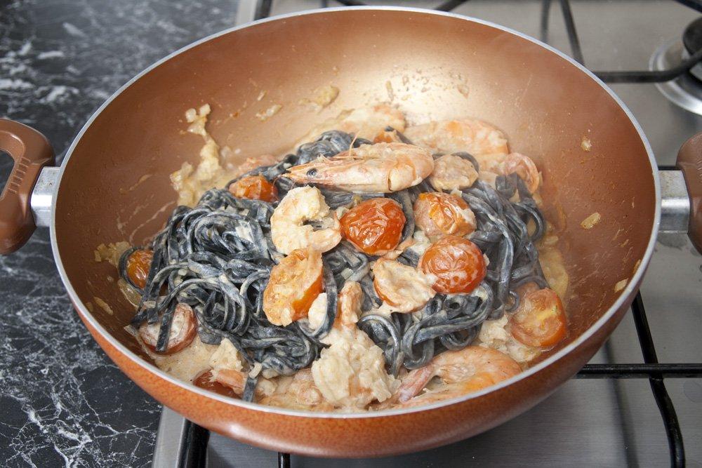 Cuociamo i tagliolini al nero di seppia e versiamoli nella pentola con il condimento.
