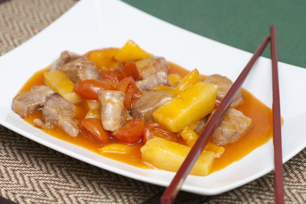 Serviamo il maiale in agrodolce con abbondante salsa.