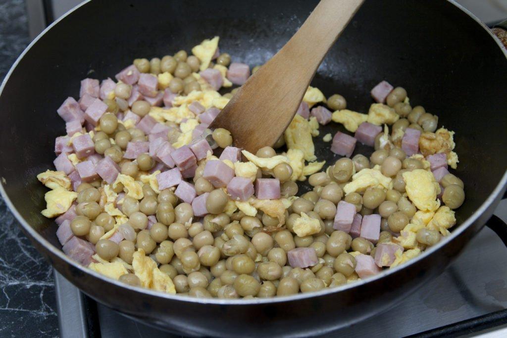 Aggiungiamo alle uova i dadini di prosciutto cotto e i piselli.