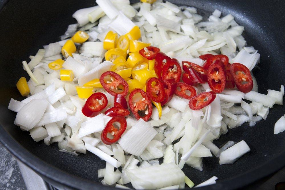 Saltiamo in olio di semi la cipolla sminuzzata e i peperoncini piccanti.
