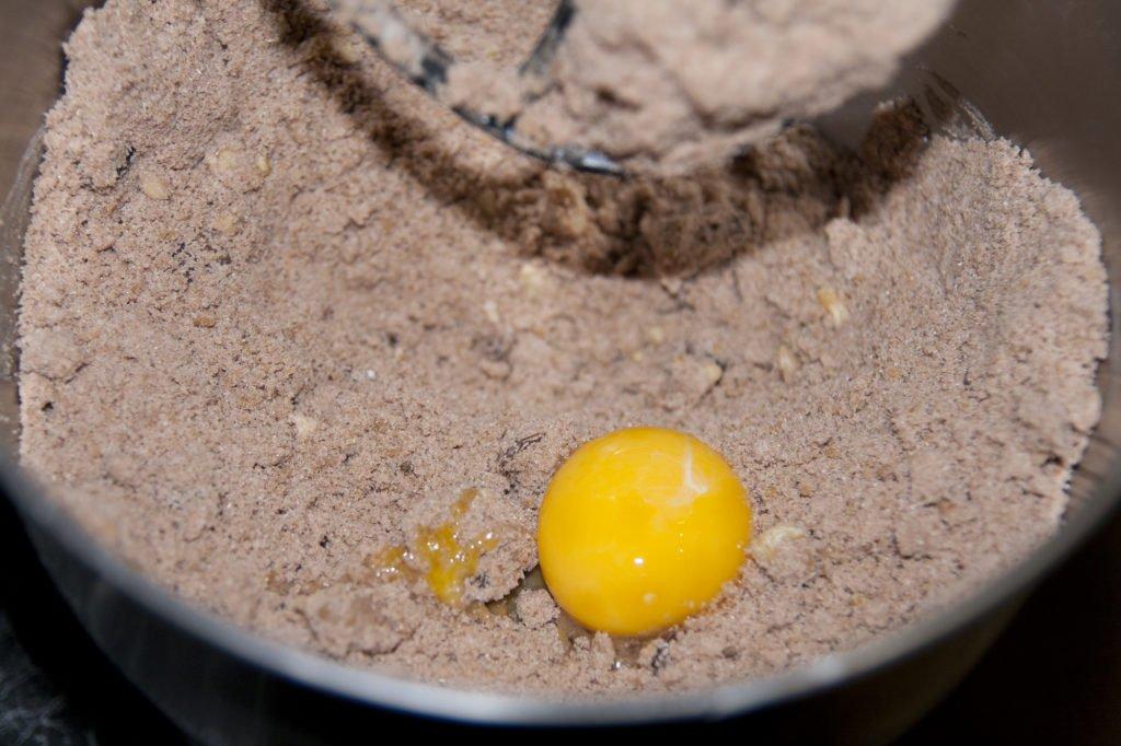 Aggiungiamo uno alla volta i tuorli, mano a mano che vengono incorporati nell'impasto dei biscotti alla cannella.