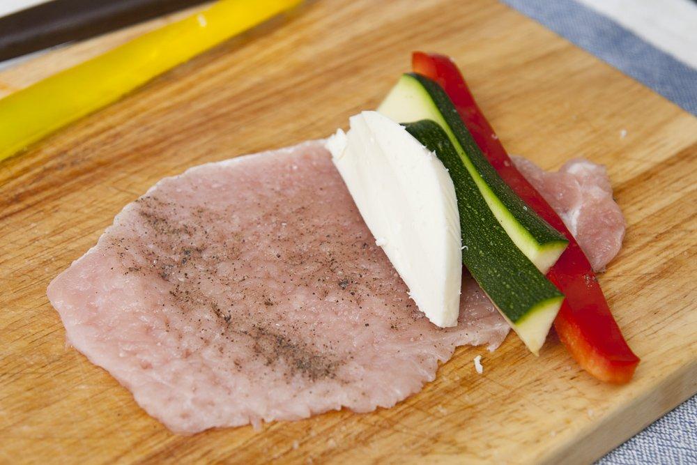 Spolverizziamo con sale e pepe per insaporire e aggiungiamo le striscioline di zucchina, peperone e scamorza.