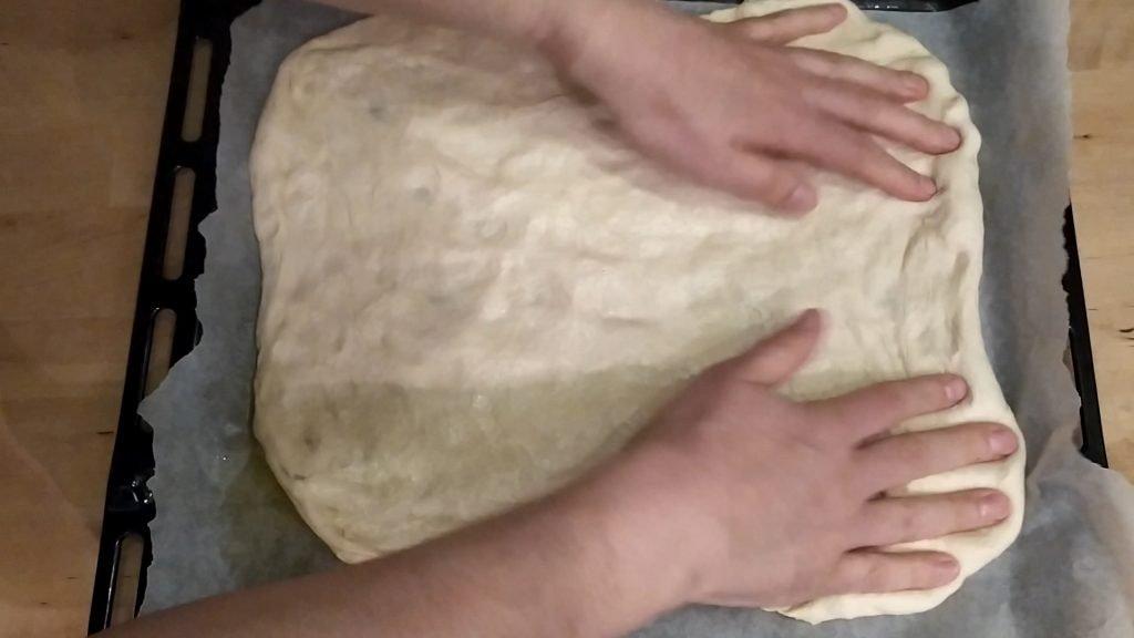 Schiacciare l'impasto della focaccia con la punta delle dita per stenderlo