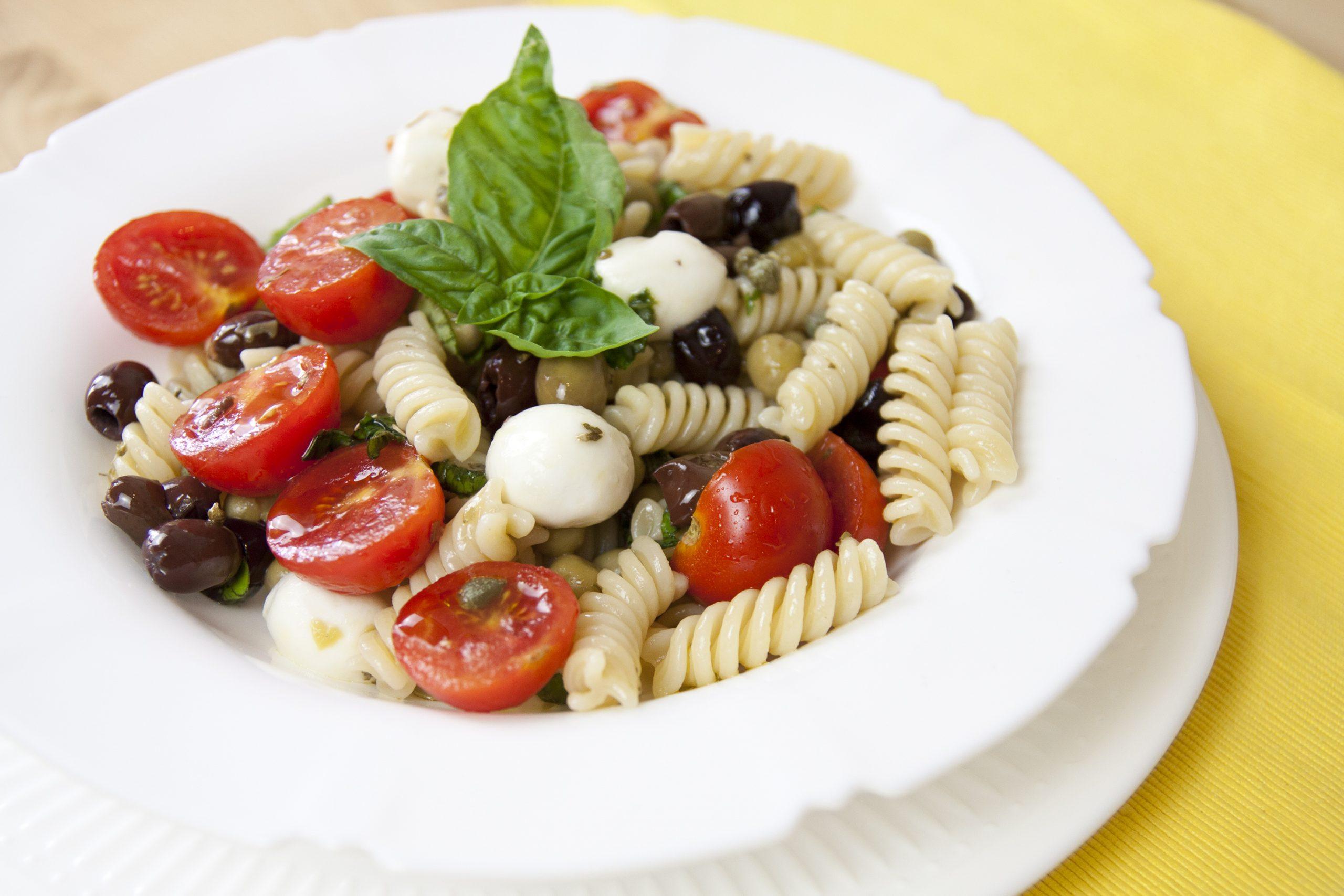 Pasta fredda con mozzarella, pomodorini, olive, capperi e piselli.