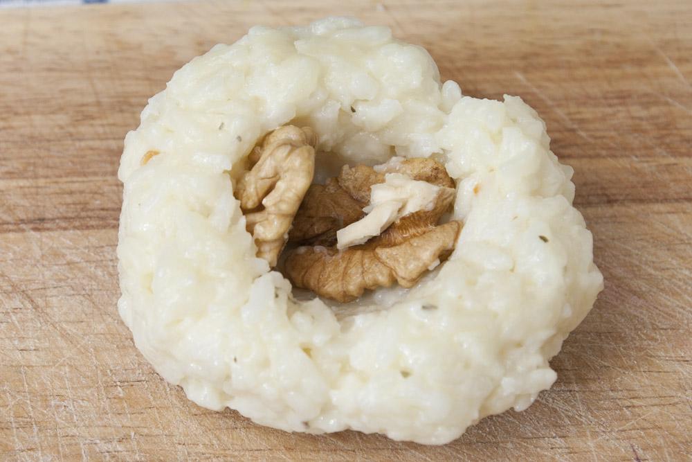 Formare le polpette di riso e farcire con taleggio e noci